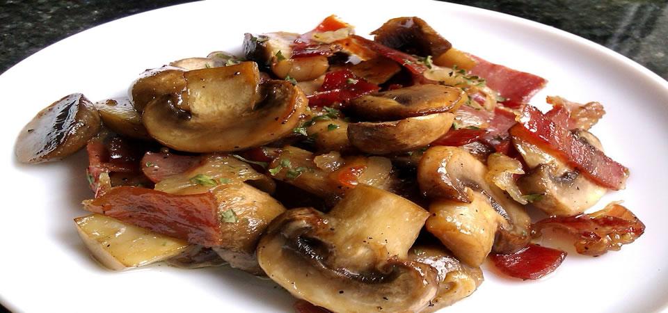 Plat de champignons avec une sauce à l'ail pilé et à l'huile avec jambon ibérique